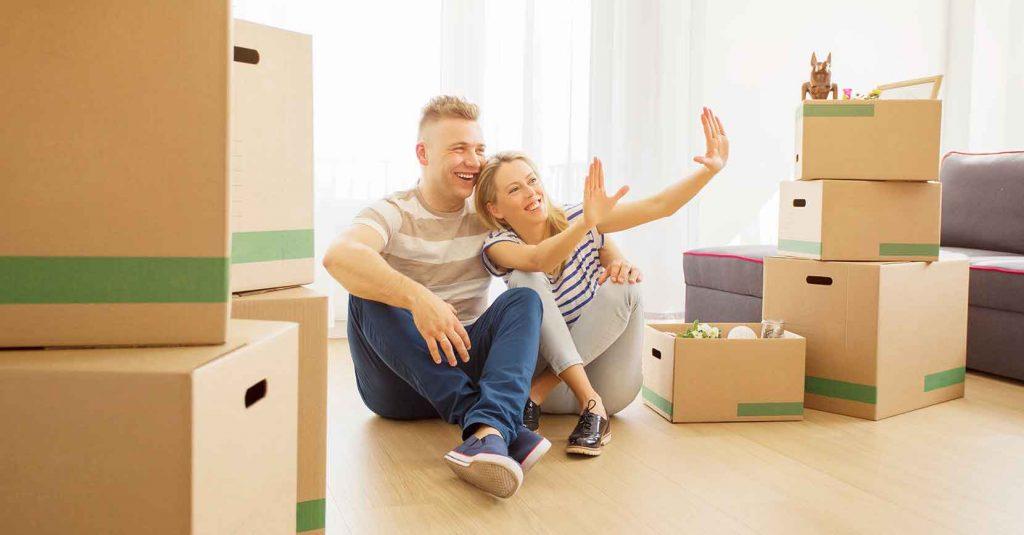 hymyilevä pariskunta asunnossa. teksti käsittelee yleistä asumistukea
